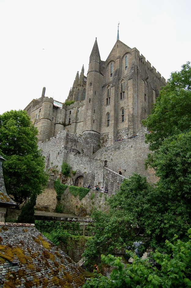 Abbey of  Mont Saint-Michel above the rooftops (note the protest banner).