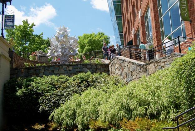 """""""Ten Artispheres"""" seen from Riverwalk, above a bank of Virginia sweetspire (Itea virginica) and other ornamentals."""
