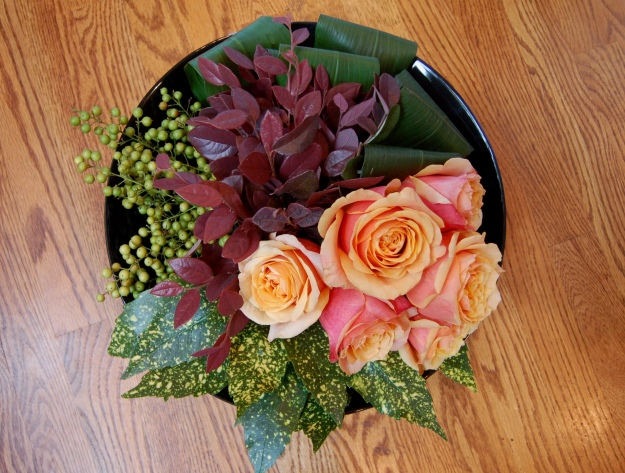 Seen from above, the arrangement features florist roses along with foliage and berries from my garden.