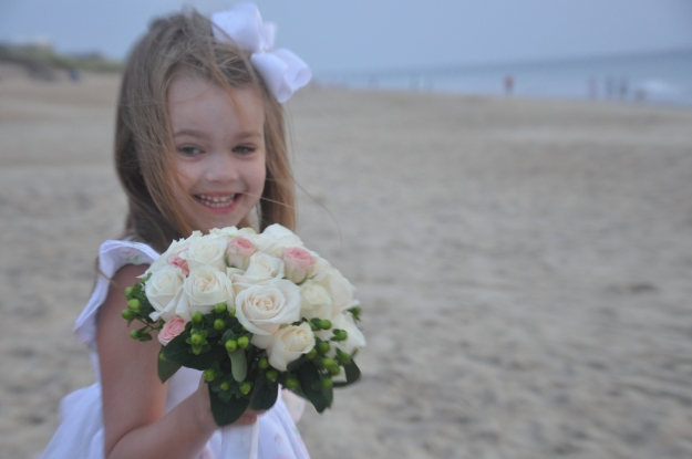 "Our ""little miss"" holding the bouquet for the bride."